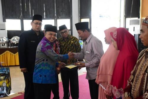 Wakil Bupati Way Kanan Edward Anthony, saat menyerahkan buku nikah secara simbolis. (Foto: Yasir)